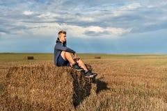 Молодой парень сидя на стоге соломы уныло смотря заботливо в расстояние с небом дождя и радугой на предпосылке стоковые изображения