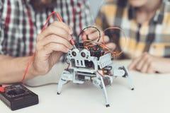 Молодой парень смотрит с наслаждением по мере того как человек проводит измерения управления представления ` s робота Стоковые Изображения