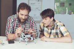 Молодой парень смотрит с наслаждением по мере того как человек проводит измерения управления представления ` s робота Стоковое Изображение RF