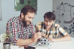 Молодой парень смотрит с наслаждением по мере того как человек проводит измерения управления представления ` s робота Стоковое Фото