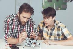 Молодой парень смотрит с наслаждением по мере того как человек проводит измерения управления представления ` s робота Стоковая Фотография RF