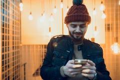 Молодой парень с бородой и smartphone в его руках На фоне ламп Стоковая Фотография