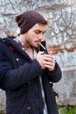 Молодой парень с курить крышки шерстей Стоковые Изображения