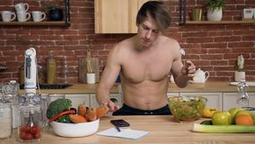 Молодой парень с нагим торсом сидит за кухонным столом есть салат vegan пока используя смартфон использующ для беседовать акции видеоматериалы
