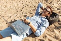 Молодой парень с стеклами, лежащ на песке, работая на его компьтер-книжке на пляже, против моря, работая на каникулах, соответств стоковое изображение