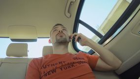 Молодой парень управляет в автомобиле и отвечает звонку видеоматериал