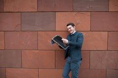 Молодой парень читает газету на фоне оранжевой стены Стоковое Фото