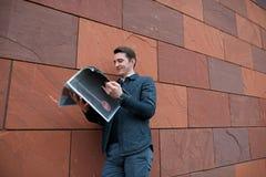 Молодой парень читает газету на фоне оранжевой стены Стоковые Фото