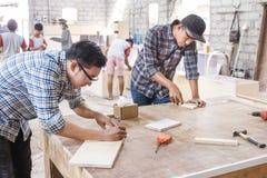 Молодой плотник измеряя и отмечать деревянную доску стоковое фото rf