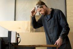 Молодой плотник работая на лесопилке на механическом инструменте Стоковое фото RF