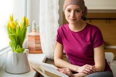 Молодой положительный онкологический больной взрослой женщины сидя в кухне окном читая книгу, усмехаясь стоковые изображения