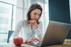 Молодой предприниматель женский используя мобильный ноутбук для смотреть новое решение дела во время процесса работы на офисе Зап стоковые фотографии rf