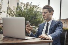 Молодой привлекательный бизнесмен держа мобильный телефон в руке стоковые изображения