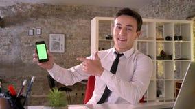 Молодой привлекательный бизнесмен работает с smartphone в офисе, показывая зеленый экран, пункт на ем, концепция дела сток-видео