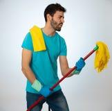 Молодой привлекательный гордый mop удерживания человека как микрофон имея потеху пока очищающ стоковое фото
