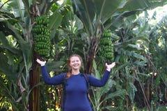 Молодой привлекательный женский путешественник стоит рядом с ладонью банана стоковые фото