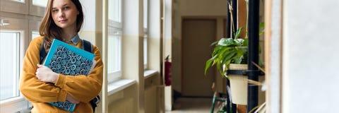 Молодой привлекательный женский студент средней школы готовя окно в прихожей на ее школе самостоятельно стоковая фотография