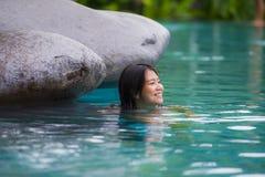 Молодой привлекательный и красивый азиатский китайский ослаблять женщины счастливый на тропическом плавании пляжного комплекса на стоковое фото rf