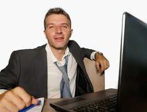 Молодой привлекательный и счастливый бизнесмен в деятельности костюма и галстука на столе ноутбука офиса изолированном на белой п стоковые фото