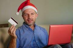 Молодой привлекательный и счастливый человек в шляпе рождества Санта Klaus используя ноутбук для покупки настоящих моментов и под стоковые фотографии rf