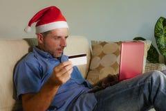Молодой привлекательный и счастливый человек в шляпе рождества Санта Klaus используя ноутбук для покупки настоящих моментов и под стоковые изображения