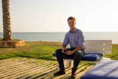 Молодой привлекательный и счастливый человек сидя и держа стекло с спиртом и усмехаться стоковая фотография rf