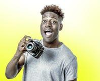 Молодой привлекательный и холодный счастливый черный афро американский человек держа цифровой рефлекторный усмехаться камеры фото стоковое изображение