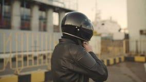 Молодой привлекательный мотоциклист человека с его шлемом и мотоцикл таможни на улице сток-видео