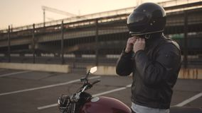 Молодой привлекательный мотоциклист человека с его шлемом и мотоцикл таможни на улице видеоматериал