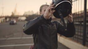 Молодой привлекательный мотоциклист человека с его шлемом и мотоцикл таможни на улице акции видеоматериалы