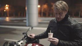 Молодой привлекательный мотоциклист человека с его шлемом и мотоцикл таможни на улице ночи акции видеоматериалы