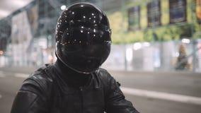 Молодой привлекательный мотоциклист человека с его шлемом и мотоцикл таможни на улице ночи сток-видео