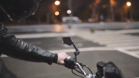 Молодой привлекательный мотоциклист человека с его шлемом и мотоцикл таможни на улице ночи видеоматериал