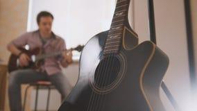 Молодой привлекательный музыкант составляет музыку на запачканных гитаре и играх, другом музыкальном инструменте на переднем план Стоковая Фотография RF