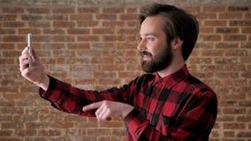 Молодой привлекательный парень с бородой говорит в videochat на smartphone, указывает, одобряет, как знак, концепцию связи акции видеоматериалы