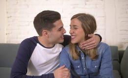 Молодой привлекательный счастливый и романтичный усмехаться кресла предложения объятия парня и подруги пар дома шаловливый в крас Стоковые Фотографии RF