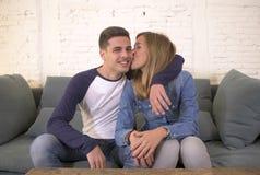 Молодой привлекательный счастливый и романтичный усмехаться кресла предложения объятия парня и подруги пар дома шаловливый в крас Стоковое Изображение RF