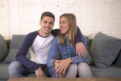 Молодой привлекательный счастливый и романтичный усмехаться кресла предложения объятия парня и подруги пар дома шаловливый в крас Стоковые Фото