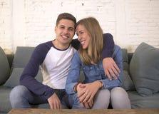 Молодой привлекательный счастливый и романтичный усмехаться кресла предложения объятия парня и подруги пар дома шаловливый в крас Стоковая Фотография RF