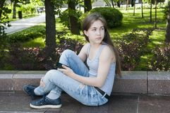 Молодой привлекательный телефон пользы девушки на стенде облака над валами лета парка белыми фото Стоковое Изображение RF