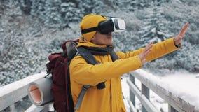 Молодой привлекательный человек в желтой куртке наслаждаясь шлемофоном стекел виртуальной реальности или игрой 3d outdoors на гор