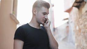 Молодой привлекательный человек идя вокруг города говорит на smartphone сток-видео