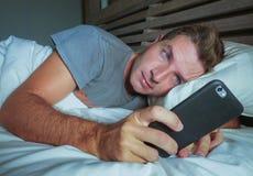 Молодой привлекательный человек лежа на кровати на ноче используя социальные средства массовой информации app на мобильном телефо стоковая фотография