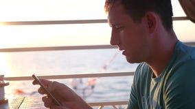 Молодой привлекательный человек сидит с телефоном в его руках на заходе солнца около моря, управляет его пальцем через видеоматериал