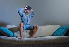 Молодой привлекательный человек gamer используя технологию headgear изумлённых взглядов VR играя видеоигру имитатора 3D имея поте стоковое изображение rf