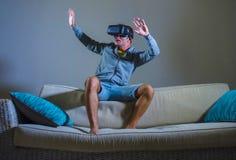 Молодой привлекательный человек gamer используя технологию headgear изумлённых взглядов VR играя видеоигру имитатора 3D имея поте стоковое фото rf