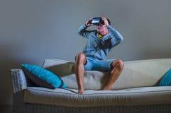 Молодой привлекательный человек gamer используя технологию headgear изумлённых взглядов VR играя видеоигру имитатора 3D имея поте стоковое изображение