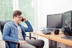 Молодой программист говоря на мобильном телефоне стоковая фотография