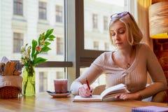 Молодой производитель сидит в кафе, составляющ игру, думающ о нюансах, писать мысли в тетради стоковая фотография rf