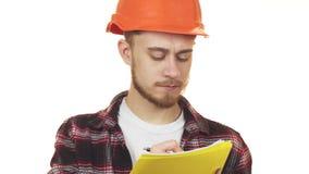 Молодой профессиональный мужской архитектор в защитном шлеме делая примечания стоковое фото
